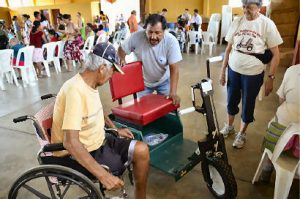 An amputee receives a PET to enhance his mobility in Guatemala. Oftentimes, regular wheelchairs aren't well suited for rough rural terrain where PET recipients live.