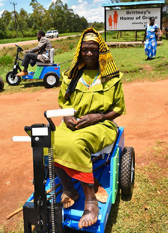 Many receive a Mobility Cart (PET) through our partner, Kenya Relief including this woman with a left foot problem and the man in the background with one leg.