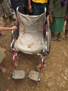 Worn and unsuitable wheelchair for rough terrain.